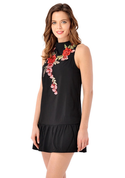 Model poses wearing black mock neck floral embroidered dress