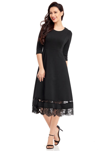 Model poses wearing black scallop hem lace panel skater dress