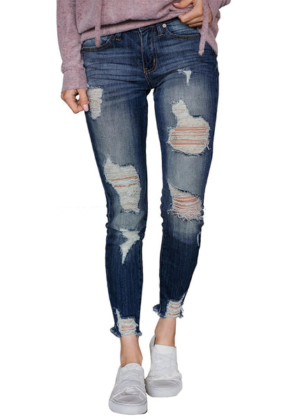 Model poses wearing blue raw hem distressed cropped skinny jeans