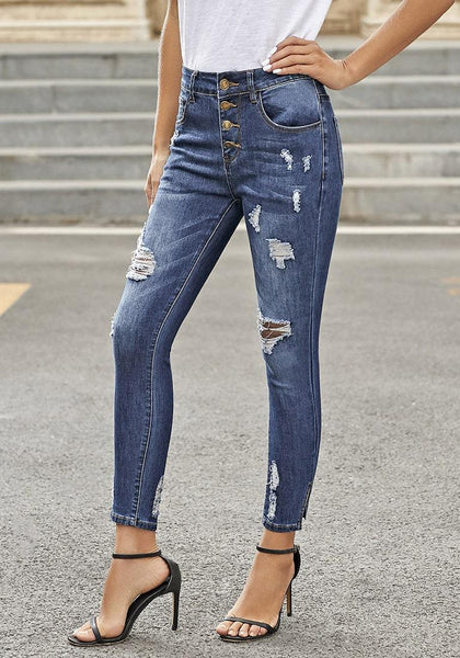 Model poses wearing dark blue high-rise buttoned distressed denim skinny jeans