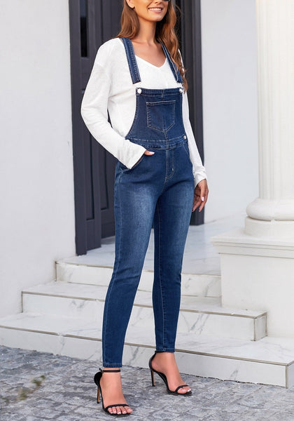 Model poses wearing dark blue rolled hem skinny denim bib overall jumpsuit