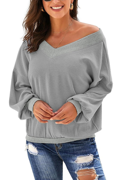 Model poses wearing grey V-neckline long batwing sleeves knit pullover