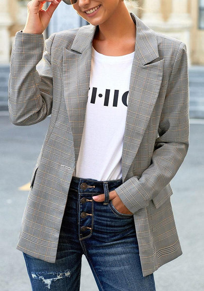 Model poses wearing grey plaid lapel front-button side-pockets blazer