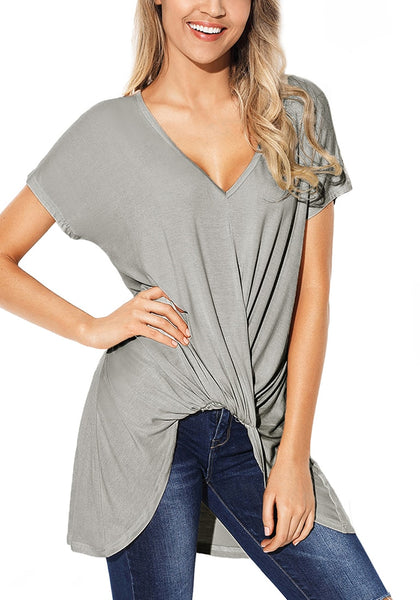 Model poses wearing grey twist-front high-low blouse