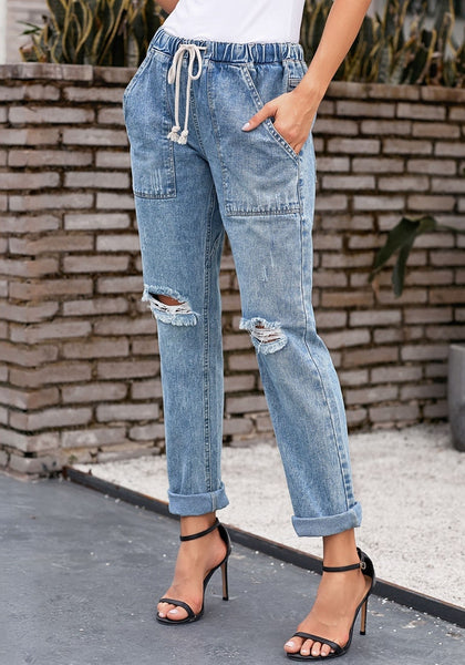 Model poses wearing light blue drawstring-waist cuffed ripped boyfriend jeans