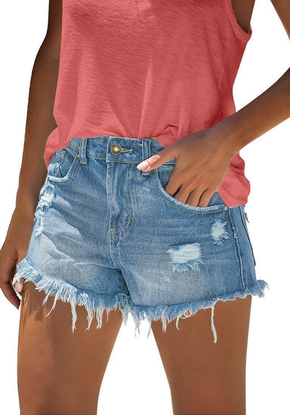 Model poses wearing light blue frayed raw hem ripped denim shorts