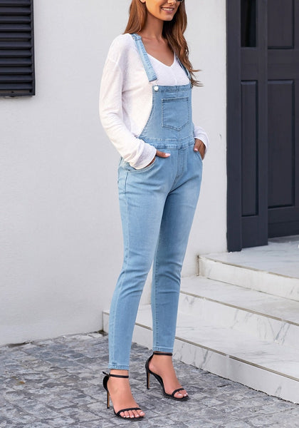 Model poses wearing light blue rolled hem skinny denim bib overall jumpsuit