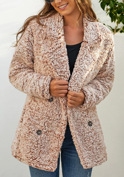 Model poses wearing light brown notched lapel double breasted fuzzy fleece coat