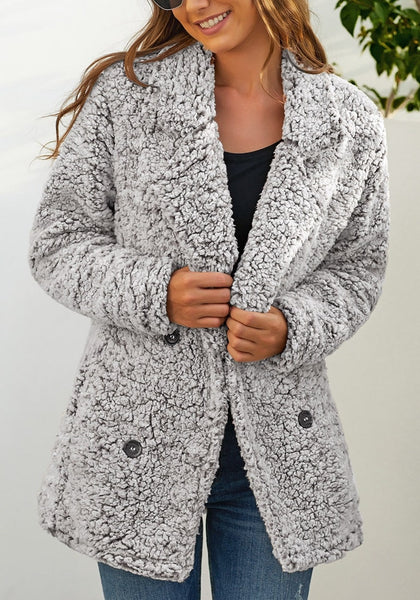 Model poses wearing light grey notched lapel double breasted fuzzy fleece coat