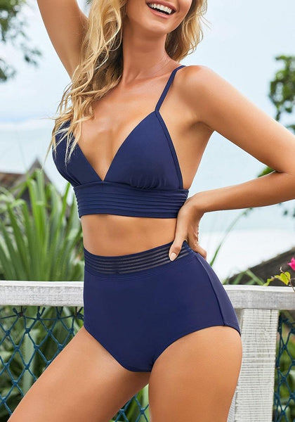 Model poses wearing navy blue elastic panel high-waist swim bottom with her triangle top