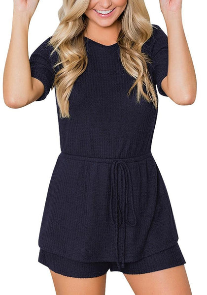 Model poses wearing navy crew neck overlay drawstring knit romper