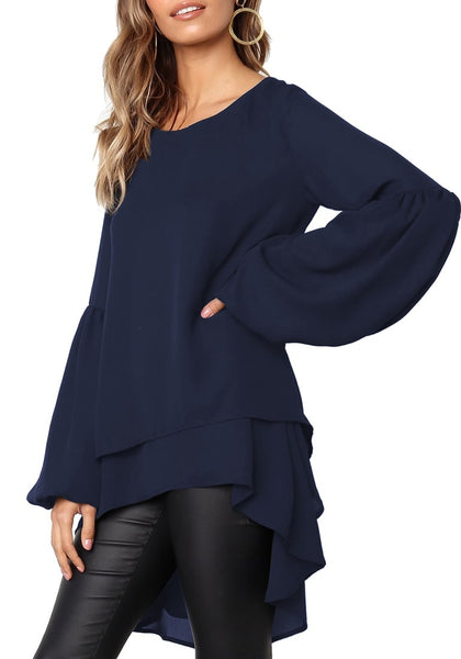 Model poses wearing navy long lantern sleeves layered high-low blouse