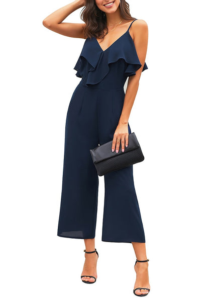 Model poses wearing navy ruffled spaghetti-strap surplice jumpsuit's