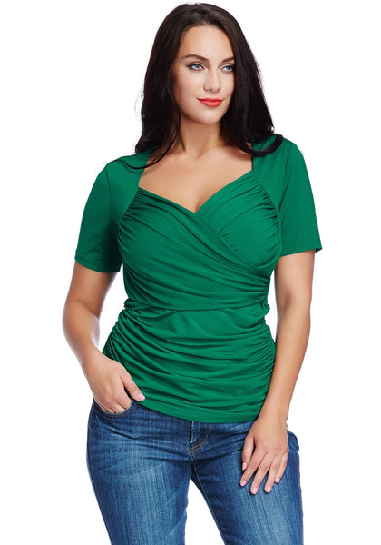 Model poses wearing plus size green ruched surplice top