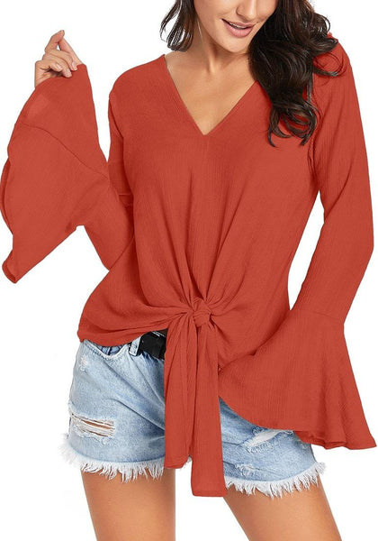 Model poses wearing rust V-neck trumpet sleeves tie-front blouse
