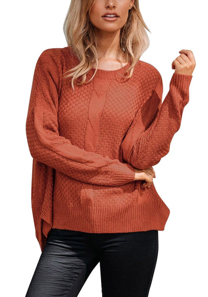 Model poses wearing rust red ribbed knit textured side-slit sweater