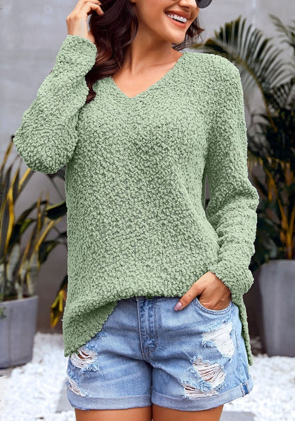 Model poses wearing sage green V-neckline popcorn fuzzy fleece pullover sweater