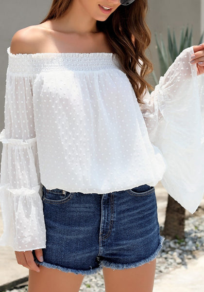 Model poses wearing white bell sleeves dotted loose off-shoulder top
