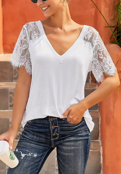 Model poses wearing white crochet lace short sleeves V-neckline top