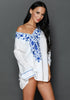 Model poses wearing white floral embroidered v neck beach cover-up