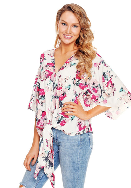Model poses wearing white floral print tie front chiffon blouse.