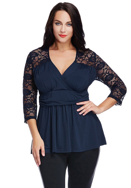 Model poses with one hand on the waist wearing plus size navy lace navy wrap top