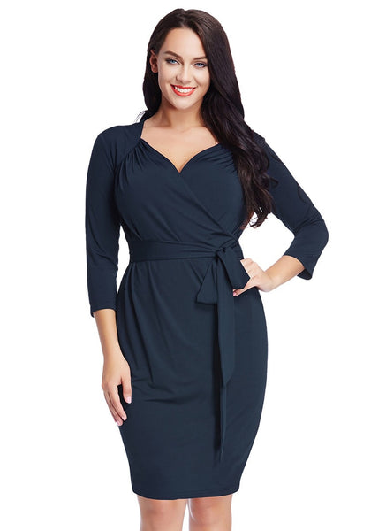 Model poses with one hand on the waist wearing plus size navy sweetheart wrap midi dress