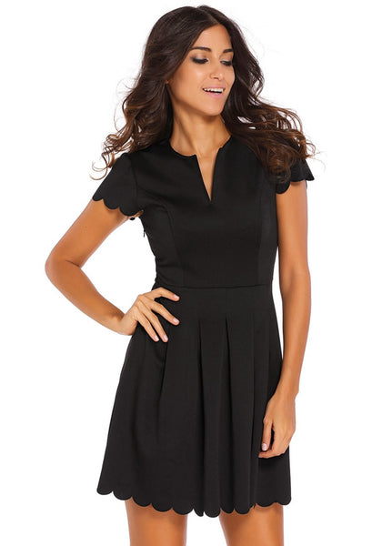 Model poses with one hand on waist wearing black scallop hem skater dress