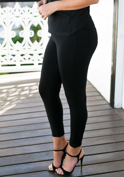 Model's left lower half with black plus-size leggings