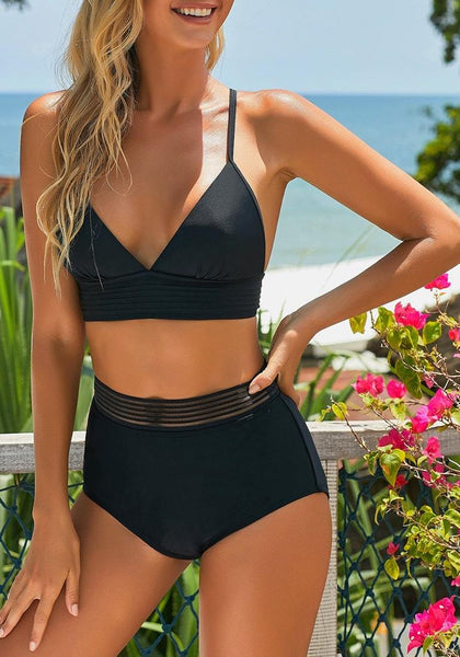 Model wearing black elastic panel high-waist swim bottom with her triangle top