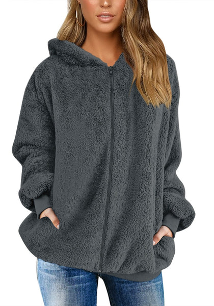 Model wearing dark grey fuzzy fleece hooded oversized coat with hoods on