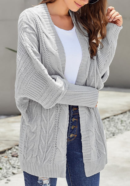 Model wearing light grey open-front oversized cable knit cardigan