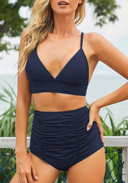 Model wearing navy blue high-waist shirred swim bottom