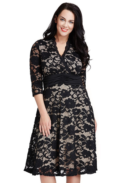 Model wearing plus size apricot lace surpliced ruched-waist dress poses with head tilted on one side