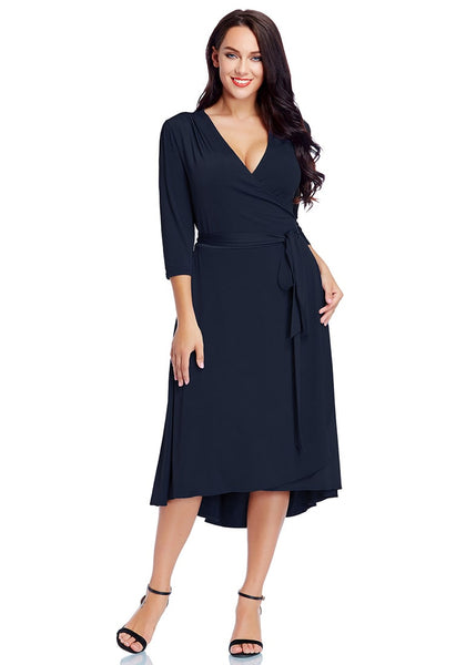 Model wearing plus size navy high-low wrap skater dress