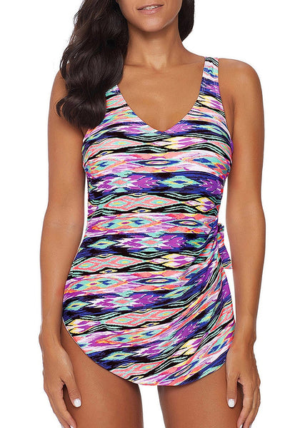 Model wearing purple side-knot overlay abstract-print swimsuit