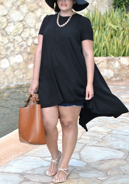 Model wears black hi-lo trapeze tunic with cutoff shorts and sandals