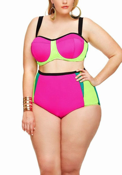 Model wears neon pink and green bikini set with one hand on hip
