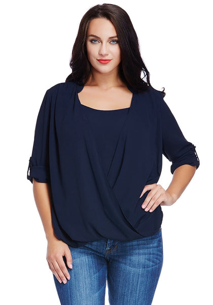 Model wears plus size navy blue Mandarin collar surplice shirt with one hand on hip