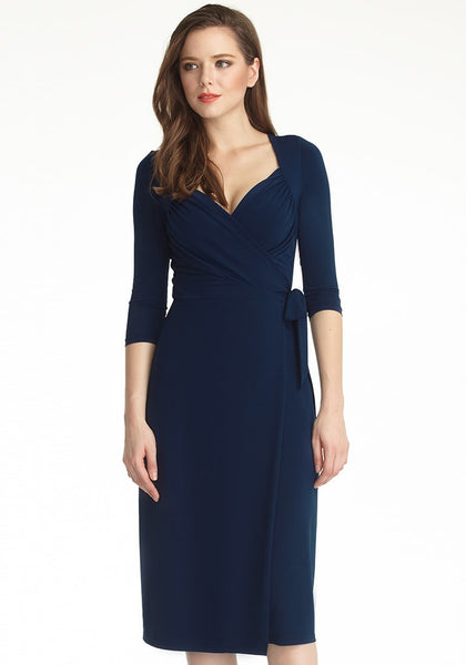 Model poses in navy blue sweetheart neckline wrap dress