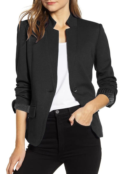 Model poses wearing black single button inverted lapel flap pockets blazer