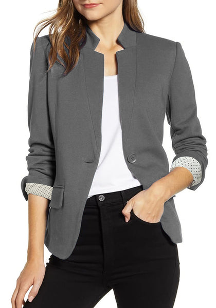 Model poses wearing grey single button inverted lapel flap pockets blazer