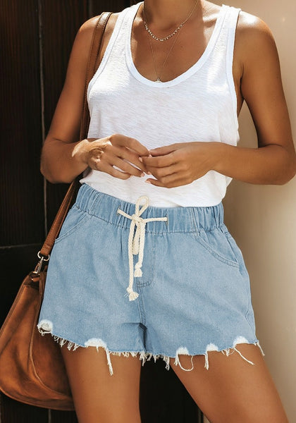 Model poses wearing light blue raw hem high-waist drawstring denim shorts