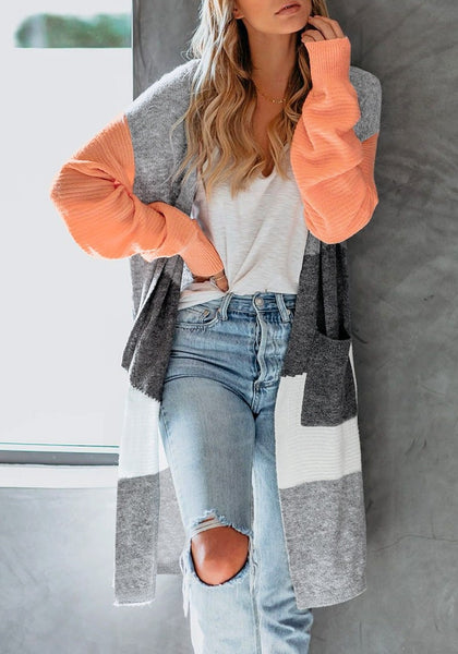 Model poses wearing orange open-front colorblock oversized long knit cardigan