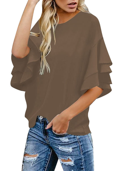 Angled shot of model wearing brown trumpet sleeves keyhole-back blouse