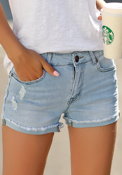Model wearing light blue frayed roll-hem ripped denim shorts
