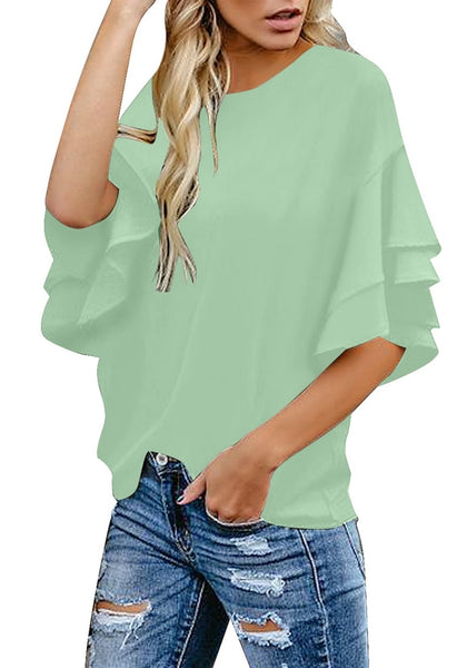 Angled shot of model wearing mint green trumpet sleeves keyhole-back blouse