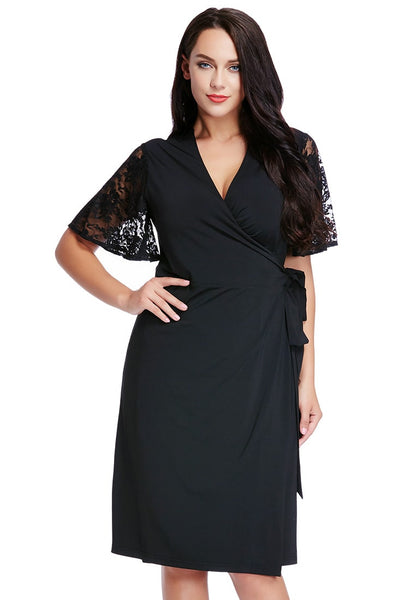 Plus size model poses in plus size black plunge wrap-style dress with one hand at waist