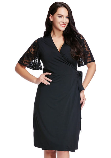Plus size model poses in plus size black plunge wrap-style dress with one hand on hip