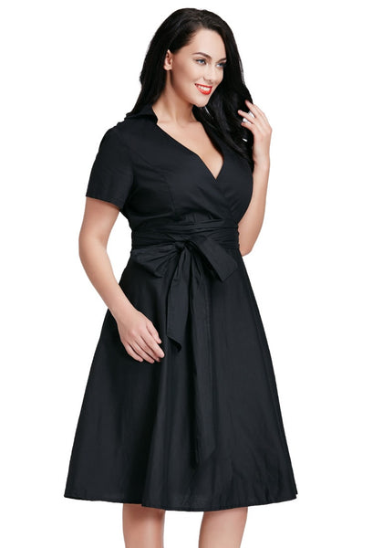 Right angle shot of model in plus size black surplice midi dress